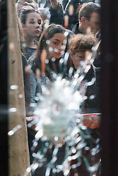 © Licensed to London News Pictures. 15/11/2015. Paris, France. Mourners through a bullet hole on Café Bonne Biére's window in Paris, France following the Paris terror attacks on Sunday, 15 November 2015. Photo credit: Tolga Akmen/LNP