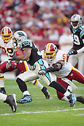 LANDOVER, MD - NOVEMBER 26:  Running back DeAngelo Williams #34 of the Carolina Panthers tries to avoid a tackle by linebacker Marcus Washington #53 of the Washington Redskins at FedExField on November 26, 2006 in Landover, Maryland. The Redskins defeated the Panthers 17-13. ©Paul Anthony Spinelli *** Local Caption *** DeAngelo Williams;Marcus Washington