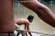 A man is fishing in a river with a bamboo fishing pole in Siem Reap, Cambodia.