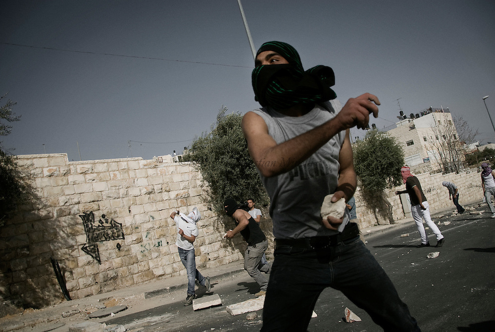 Masked Palestinian throws a stone  in  East Jerusalem neighboorhood of Ras al-Amud March 12, 2010. Israeli forces sealed off the West Bank and massed riot squads around Jerusalem's Old City and Arab neighboorhoods during Muslim weekly prayers on Friday, facing down Palestinian anger over Jewish settlement expansion.