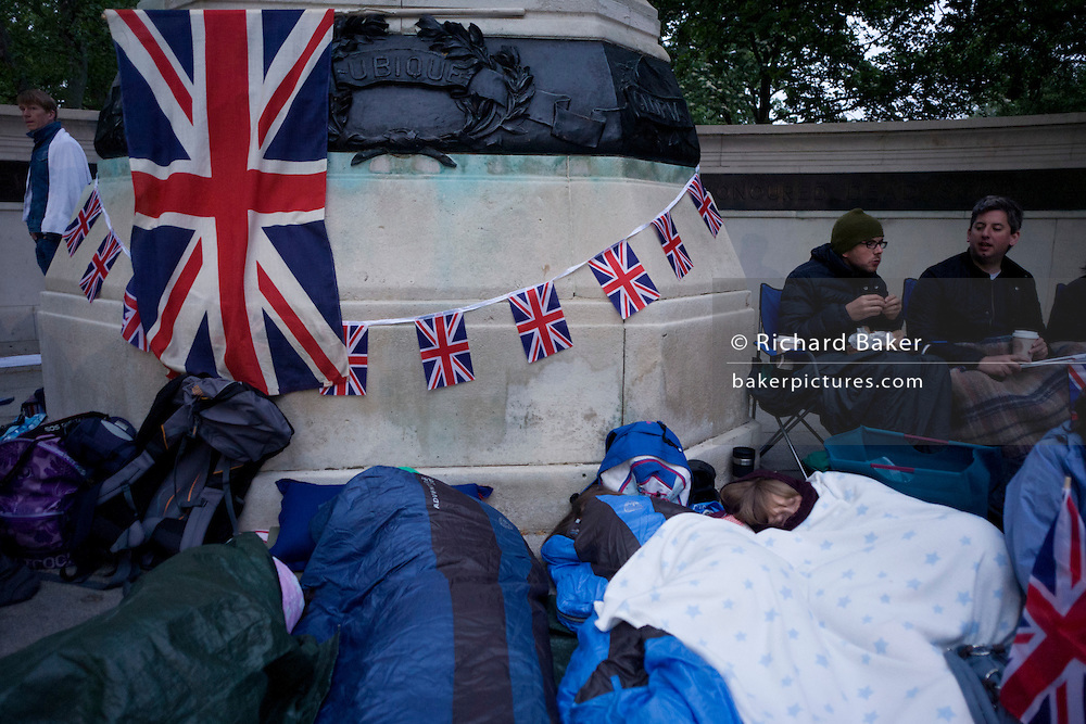 Royalist enthusiasts camp outdoors beneath a French war memorial in the Mall, in the hours before the royal marriage of Prince William and Kate Middleton. Dawn light reveals a massed crowd of Britons and foreign visitors (many Americans and Commonwealth citizens)  who are asleep in small tents and warm under sleeping bags. Taking place on Friday 30th April in front of millions the crowds are already gathering to claim their ideal locations in the front rows along the procession route later that morning.