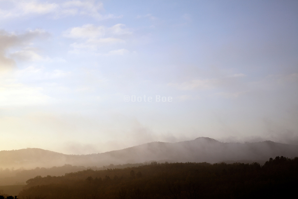 hilly landscape with early morning fog rising up