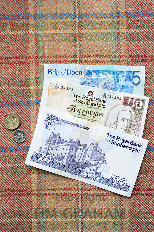 Scottish banknotes from The Royal Bank of Scotland £5, £10 £20 £1 5p coins on traditional Scottish tartan background