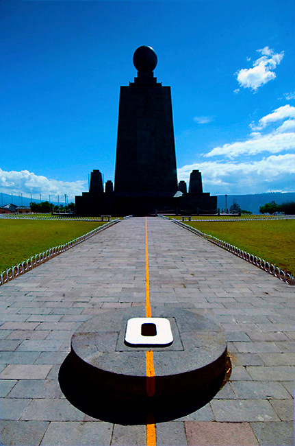 A monument and orange line with an east facing stone marker identifies Ecuador's biggest claim to fame, its location on the equator.  The monument is called the La Mitad del Mundo or The Middle of the World and marks the equatorial line.