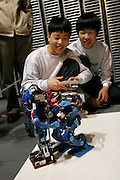 ROBOT FIGHTS. Gathering where kit-made robots fight while remote controlled by their owners. here two brothers worming up their robot before the real fight.