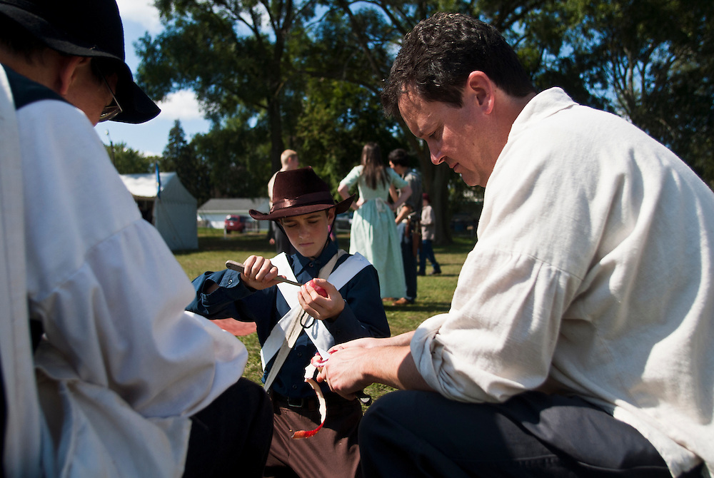 Lathan Goumas | The Bay City Times..Adam Samyn, 13, peels and apple as a member of the Mormon battalion that fought in the Mexican-American War during the River of Time at Veterans Park in Bay City, MI., on Saturday September 24, 2011.