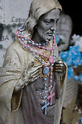 A plaster figure of Jesus draped with plastic beads and a crucifix at a gravestone in a south London cemetery.