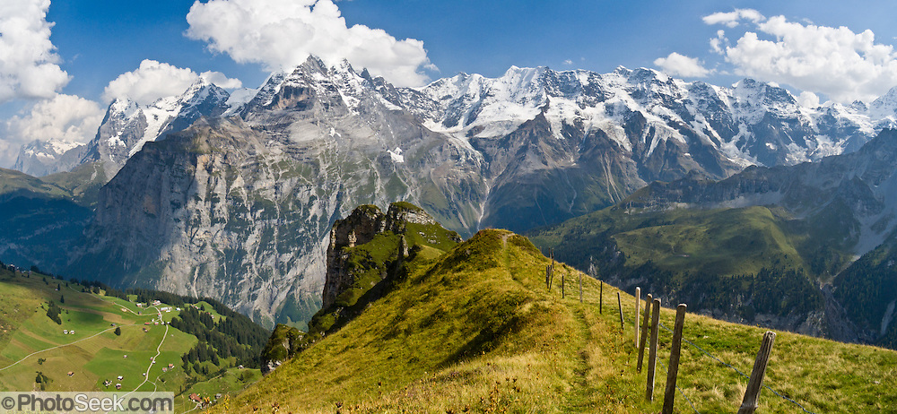 "From Wasenegg Ridge, see mountain peaks of Eiger (the Ogre, 13,026 feet), Mönch (the Monk), Jungfrau (the Virgin, 13,600 feet), and Lauterbrunnen Wall in the Berner Oberland, Switzerland, the Alps, Europe. The Bernese Highlands are the upper part of Bern Canton. Panorama stitched from 3 overlapping photos. UNESCO lists ""Swiss Alps Jungfrau-Aletsch"" as a World Heritage Area (2001, 2007)."