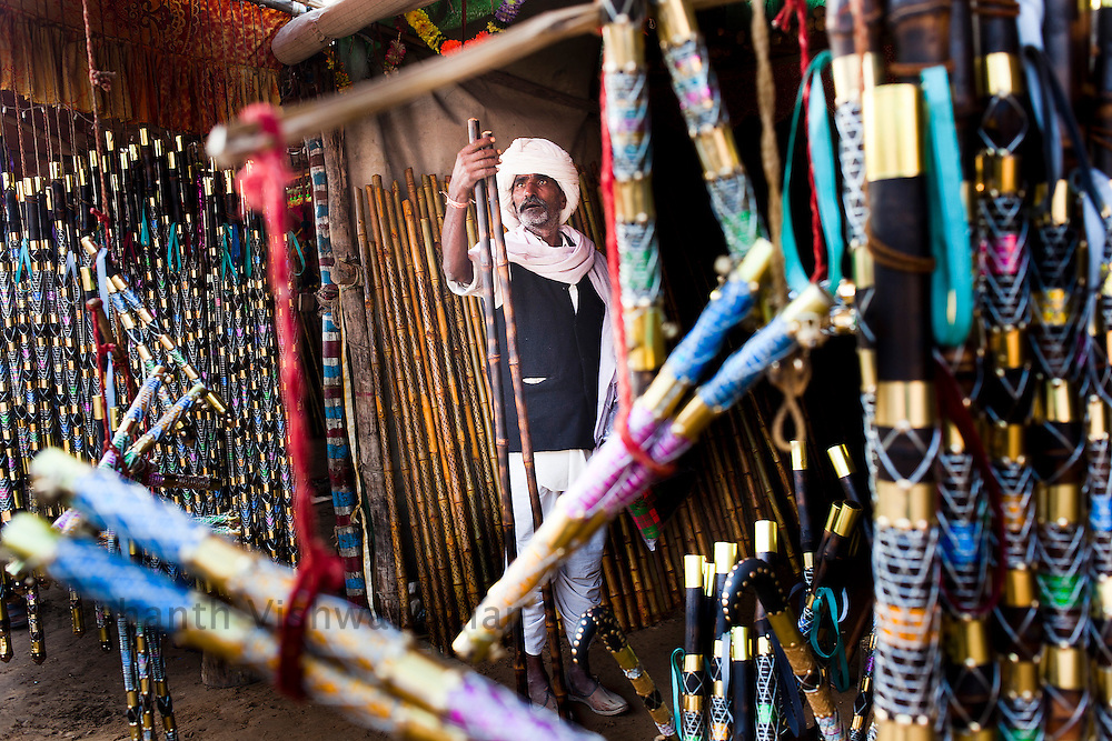 A man  checks a decorated stick used for walking as well as controlling horses and camels at the fair grounds in Pushkar, India, November 6, 2011.  Photographer: Prashanth Vishwanathan