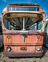 Old bus deteriorating in a junkyard.