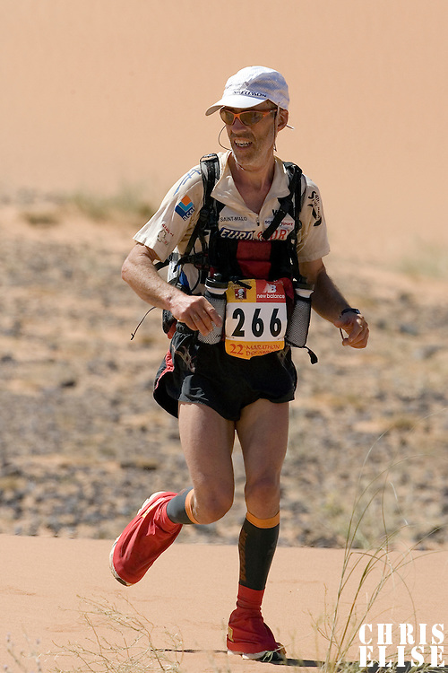30 March 2007: #266 Lionel Eveno of France runs in erg Znaigui en route to check point 3 during fifth stage of the 22nd Marathon des Sables between west of Kfiroun and erg Chebbi (26.22 miles). The Marathon des Sables is a 6 days and 151 miles endurance race with food self sufficiency across the Sahara Desert in Morocco. Each participant must carry his, or her, own backpack containing food, sleeping gear and other material.