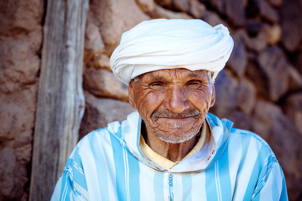 Portrait of an elderly Berber man wearing traditional Amazigh dress, sitting outside the Ait Inlatten Granary, Taliouine province of the Souss Massa Draa, Southern Morocco, 2016-05-24.<br /><br />The Inlatten 'agadir' (singular form of granary in Tamazert Amazigh dialect) is a fortified Berber collective granary.<br /><br />The journey to find each agadir is really the fun part. Whether it's stopping to meet interesting characters as you ask for directions in remote villages, finding yourself being invited to drink tea at a home during rains, or laughing as you weigh up the tales told by key keepers concerning the secrets of the agadirs, these incredible structures make for an amazing thread to any trekking route through the Anti Atlas.