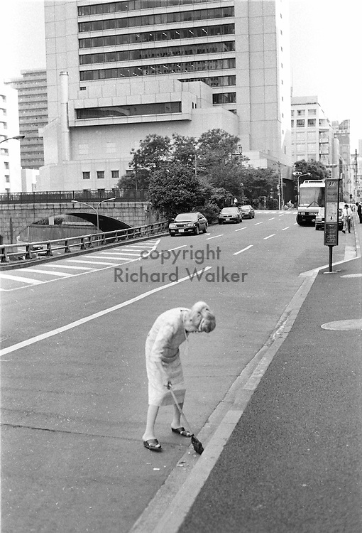 An elderly woman sweeps a Ginza side street. Ginza, Tokyo,  August, 1998. By Richard Walker