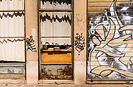 Faded curtains and books in a shop window, on a graffiti painted back street of Venice, Italy