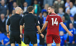 Liverpool's Jordan Henderson speaks with officials as he leaves the pitch at half time during the Premier League match at King Power Stadium, Leicester.