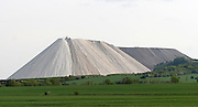 "Monte Kali: A Mountain of Table Salt<br /> <br /> Monte Kali is an unusual landmark in the small town of Heringer in eastern Hesse, Germany. It's a spoil heap containing nothing but sodium chloride or common table salt, which is a byproduct of potash mining. For over a hundred years, potash mining has been a major industry in the region. It started with the opening of Wintershall potash works, which began mining in 1903, and today is the world's biggest potash mine with an operational area about the size of Greater Munich's.<br /> <br /> Potash mining produces a mixture of potash and sodium chloride, with potassium content between 20% and 35%. Thus, for every ton of potash recovered, several tons of sodium chloride is produced. This is dumped at several sites around the region. The dumps contain up to 96% sodium chloride.<br /> Monte Kali began growing in 1973, and it's where the K+S chemical company dumps sodium chloride. The heap rises over 200 meters above the surrounding land, and as of January 2014, covered an area of 93 hectares. It contains as approximately 188 million tonnes of salt, with another 900 tonnes being added every hour and 6.4 million tonnes a year.<br /> <br /> Lying next to the border with the state of Thuringia, Monte Kali towers over Heringen and is a popular attraction. Locals refer to it as ""Kalimanjaro"" — a play of words between Kali (shorthand for Kalisalz, German for ""potash"") and the famous volcanic peak Mount Kilimanjaro. More than 10,000 visitors climb the artificial mountain every year.<br /> <br /> But Monte Kali and other spoil heaps in the region are environmentally destructive. An enormous amount of salt seeps into the ground polluting the soil, rivers and groundwater. The surrounding soil has become virtually barren and only a few halophyte plants resistant to salt can grow there. The Werra river too has become inhospitable to freshwater organisms.<br /> ©Exclusivepix Media"