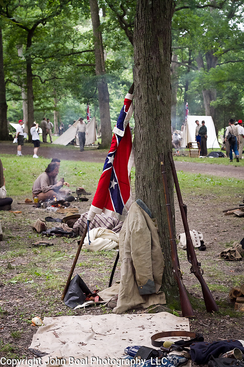 A Confederate flag, rifles and jacket rest against a tree in a living history Confederate soldiers encampment, during the Sesquicentennial Anniversary of the Battle of Gettysburg, Pennsylvania on Wednesday, July 3, 2013.  During the sesquicentennial anniversary of the Battle of Gettysburg, the encampment provided an opportunity for visitors to the park to learn about the soldiers' lives during the war.  John Boal Photography