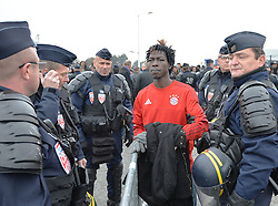 "French police officers with a migrant outside a processing centre in ""the jungle"" near Calais, northern France, as the mass exodus from the migrant camp begins."