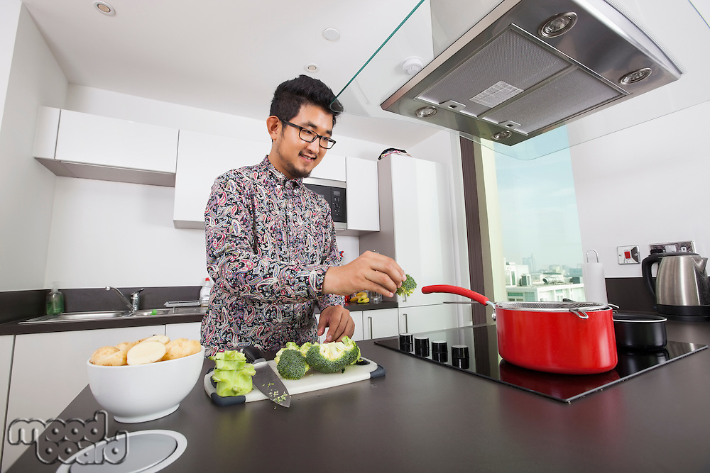 Smiling man cooking in kitchen at home