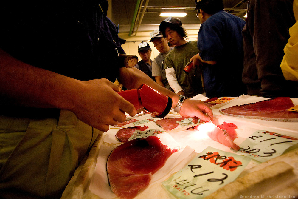 Tuna auction. Frozen tuna arrives with fishing ships from all over the world, the buyers examine the thin slices that are cut from the tuna's tail as quality samples and at 5 am the tuna auctions begin.  Tsukiji fish market  is the biggest wholesale fish and seafood market in the world and also one of the largest wholesale food markets of any kind. The market is located in Tsukiji in central Tokyo, and is a major attraction for foreign visitors.