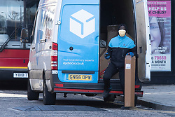 © Licensed to London News Pictures. 24/03/2020. London, UK. A delivery driver in Greenwich wears a medical mask and latex gloves . Last night the Government announced a lockdown to slow the spread of Coronavirus and reduce pressure on the NHS. Photo credit: George Cracknell Wright/LNP