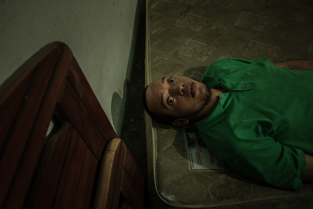 """MARACAY, VENEZUELA - JULY 4, 2016: Schizophrenic Gerardo Simeone rests on a mattress in his bedroom in the middle of the day.  He spends most of his days either sleeping, or standing in a corner in silence in his family's living room, rarely even making eye contact with members of his family.  His parents remember how he used to be when he was younger…before he became ill - recalling how affectionate and talkative he was. """"He was so kind and loving,"""" said his mother, Evelin.  Gerardo's brother Accel is also schizophrenic. Their parents spend hours each week searching pharmacies for the psychiatric drugs that thier sons need, which are very difficult to find, because of nationwide shortages.  """"I am tired,"""" Evelin said. """"This is too much sometimes"""".  PHOTO: Meridith Kohut for The New York Times"""