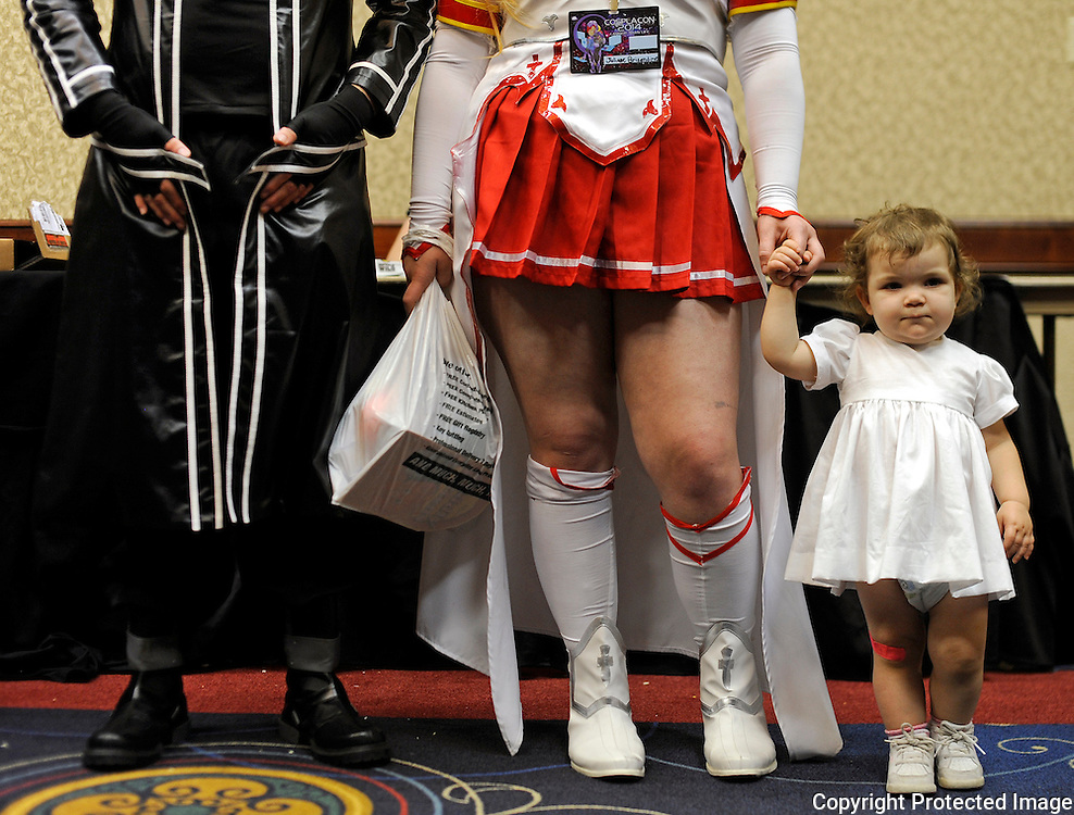 Kris Wilson/News Tribune<br /> Liliana Brizendine, right, holds her mom Juliane Brizendine's hand as they and Brandon Vaughan wait at the rear of the ballroom just before the start of the Cosplay Royale during Cosplacon 2014 at the Capitol Plaza Hotel on Saturday.