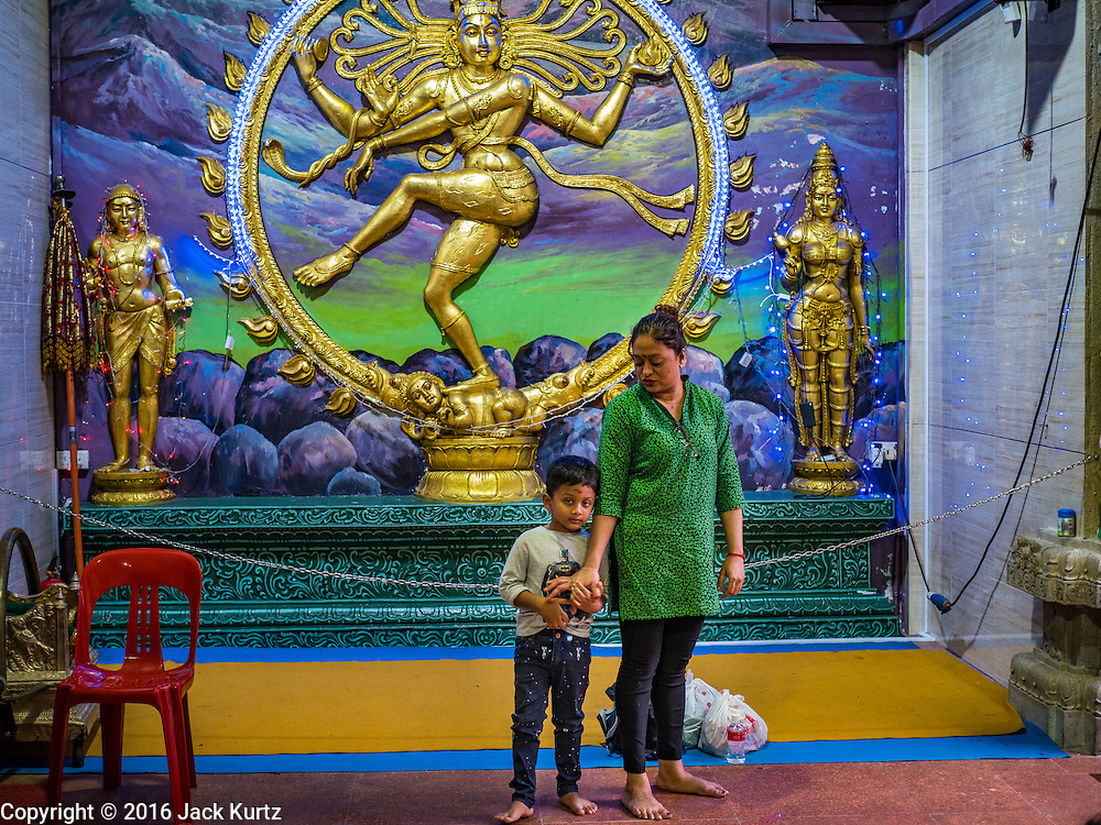 27 DECEMBER 2016 - SINGAPORE: A woman and her son before evening prayers at Sri Veeramakaliamman Temple in Singapore. It is one of the most important Hindu temples in Singapore.      PHOTO BY JACK KURTZ