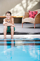 Boy sitting on edge of pool portrait