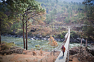 Woman walks on a footbrige crossing a river, Zangkhar village, Bhutan, Asia
