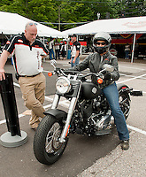 Wanda Taylor receives instruction from Doug Cross prior to heading out on a Softail Slim for her free demo ride offered by Harley Davidson at the Hart's Turkey Farm parking lot in Meredith Monday morning.   (Karen Bobotas/for the Laconia Daily Sun)