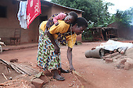 Mary Kamangeni, 52, sweeps her courtyard in Tholo, Malawi with her grandson safely strapped to her back. Mary was often hospitalized due to complications of HIV in 2007.  Her weight hovered at around 60 pounds. Anti-retrovirals and supplementary feeding restored her health and will to live. With her weight at 110 pounds, Mary vowed to work harder than anyone else in her community to provide for her family. Sara A. Fajardo/Catholic Relief Services