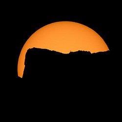 The Sun is seen as it rises behind Jack Mountain head of the solar eclipse, Monday, Aug. 21, 2017, Ross Lake, Northern Cascades National Park, Washington. A total solar eclipse will sweep across a narrow portion of the contiguous United States from Lincoln Beach, Oregon to Charleston, South Carolina. A partial solar eclipse was visible across the entire North American continent along with parts of South America, Africa, and Europe.  Photo Credit: (NASA/Bill Ingalls)