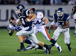 Connecticut quarterback Tyler Lorenzen (4) rushes past Virginia linebacker Denzel Burrell (45).  The Connecticut Huskies defeated the Virginia Cavaliers 45-10 in NCAA football at Rentschler Field in East Hartford, CT on September 13, 2008.
