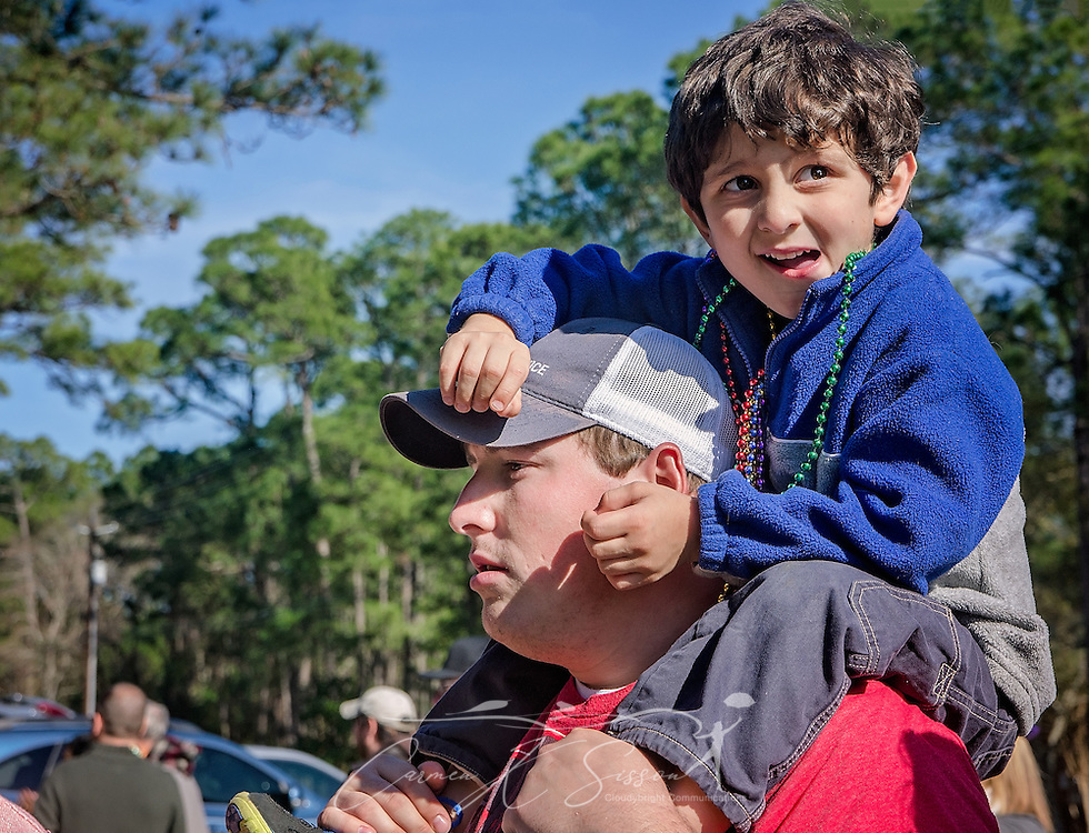 Chase Allen holds Shawn Irby, 4, on his shoulders as they watch Dauphin Island's first People's Mardi Gras Parade, Feb. 4, 2017, in Dauphin Island, Alabama. French settlers held the first Mardi Gras in 1703, making Mobile's celebration the oldest Mardi Gras in the United States. The first parade of the season is traditionally held on Dauphin Island and draws thousands. (Photo by Carmen K. Sisson/Cloudybright)