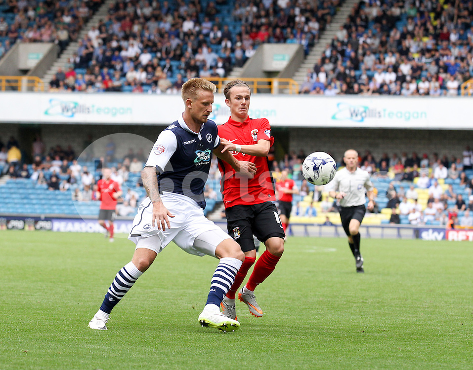 Byron Webster of Millwall plays the ball under pressure from James Maddison of Coventry City during the Sky Bet League 1 match between Millwall and Coventry City at The Den, London, England on 15 August 2015. Photo by Edmund  Boyden.