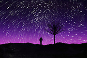 Silhouette of a man and a tree at night under a sky full of star trails<br />