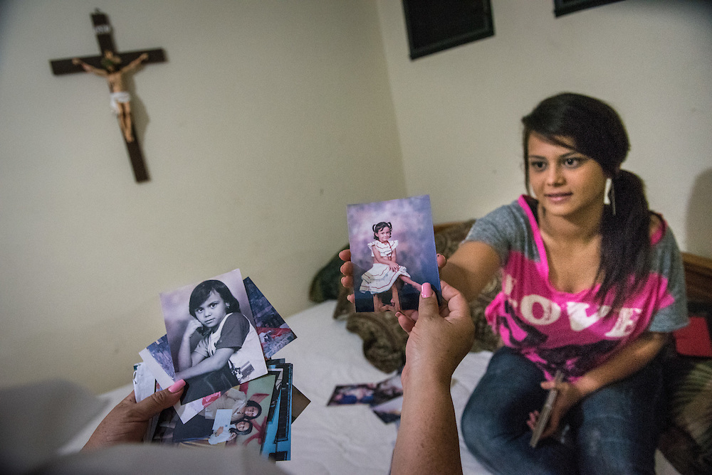 Carmen Julissa Ramirez Suarez, 18, looks at oldphotographs with her mother Gloria at a friends house in Colonial Santa Fe neighborhood of Santa Rosa de Copan October 17, 2015. Suarez hopes the Ohio doctors working with Central American Medical Outreach (CAMO) will be able to reverse the spinal problem she has had since birth. Photo Ken Cedeno