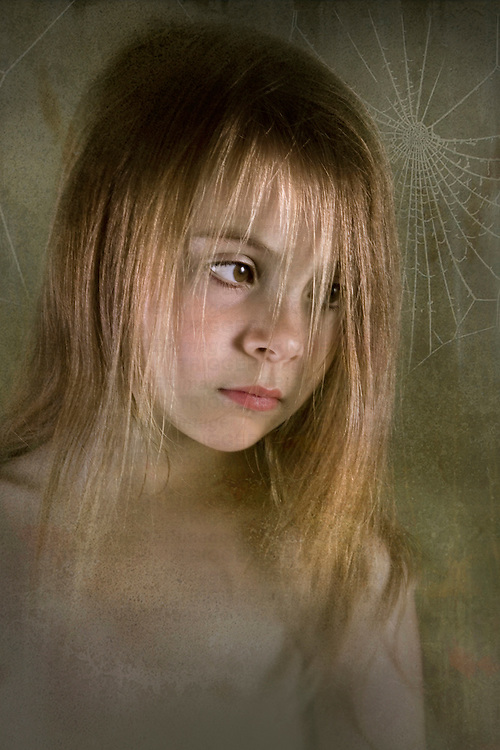 young child looking serious with cobwebs in the background