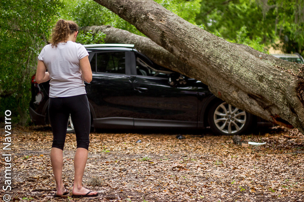 While waiting for further instructions from the insurance company, Dawson Pickett waits at the place where her less than 2-year-old SUV was crushed by a tree. (photo by Samuel Navarro)