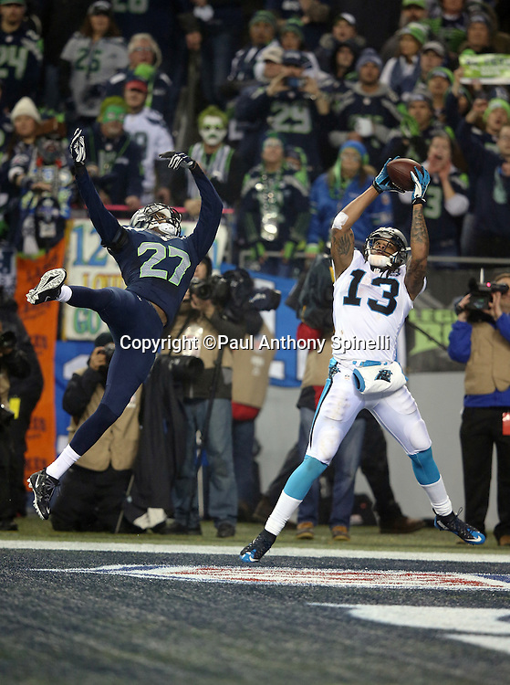 Carolina Panthers wide receiver Kelvin Benjamin (13) is covered by Seattle Seahawks cornerback Tharold Simon (27) as he catches a late fourth quarter touchdown pass that cuts the Seahawks lead to 31-17 during the NFL week 19 NFC Divisional Playoff football game against the Seattle Seahawks on Saturday, Jan. 10, 2015 in Seattle. The Seahawks won the game 31-17. ©Paul Anthony Spinelli