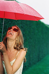 Woman laughing outdoors in the rain with a red umbrella