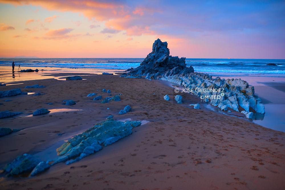 Photographer waiting for the light at the beach in Sopelana, Bizkaia, Spain