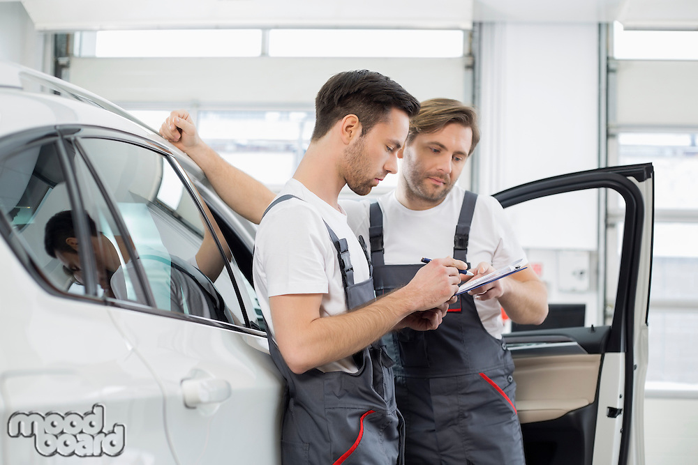 Automobile mechanics checking checklist while standing by car in workshop
