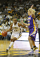 December 22 2010: Iowa guard Kachine Alexander (21) drives around Northern Iowa guard/forward Erin Brocka (44) during the first half of an NCAA college basketball game at Carver-Hawkeye Arena in Iowa City, Iowa on December 22, 2010. Iowa defeated Northern Iowa 75-64.