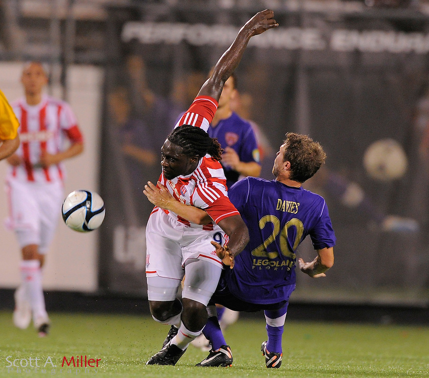 Stoke City Potters forward Kenwyne Jones (9) is tripped by Orlando City Lions defender Kyle Davies (20) as they go for a ball during the Potters 1-0 win at the Florida Citrus Bowl on July 28, 2012 in Orlando, Florida. ..©2012 Scott A. Miller.