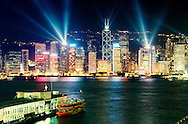 Hong Kong Island China city skyline with night laser light show seen across Victoria Harbour from Kowloon Star Ferry terminal