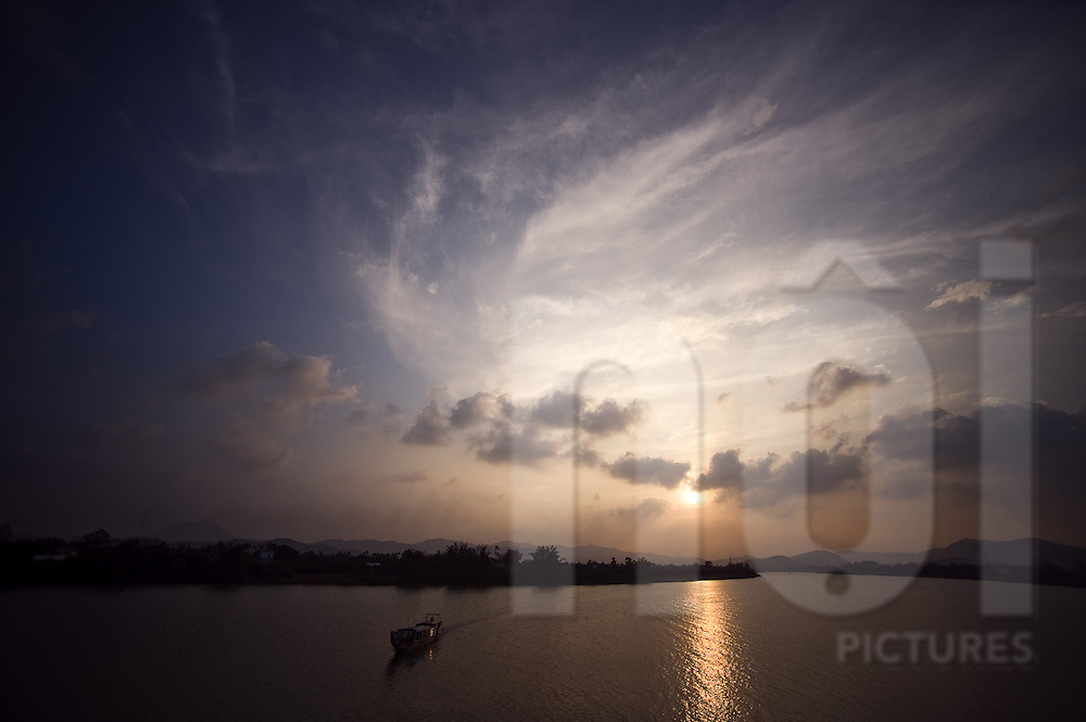 A boat sails on Perfume river at sunset. Hue, Vietnam, Asia.
