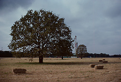 Stock photo of an on-shore drilling rig beyond a farm's hay field