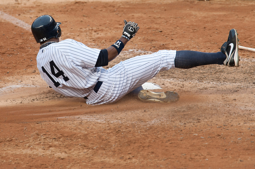 NEW YORK - AUGUST 13: Curtis Granderson #14 of the New York Yankees slides into home plate during the game against the Tampa Bay Rays at Yankee Stadium on August 13, 2011 in the Bronx borough of Manhattan. (Photo by Rob Tringali) *** Local Caption *** Curtis Granderson